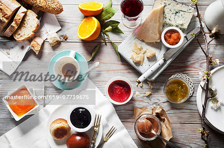 Various types of jam with cheese, bread and drinks on a wooden table Stock Photo - Premium Royalty-Free, Image code: 659-07739675