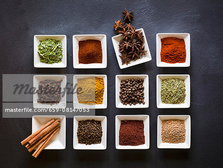 Various spices in square dishes on a chalkboard surface Stock Photo - Premium Royalty-Free, Image code: 659-08147053