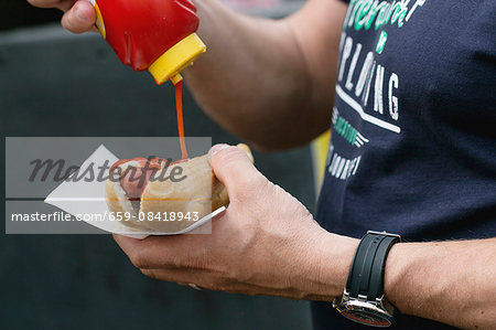 A man pouring ketchup onto a hot dog Stock Photo - Premium Royalty-Free, Image code: 659-08418943