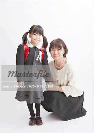 Girl carrying school bag and mother Stock Photo - Premium Royalty-Free, Image code: 670-03886158