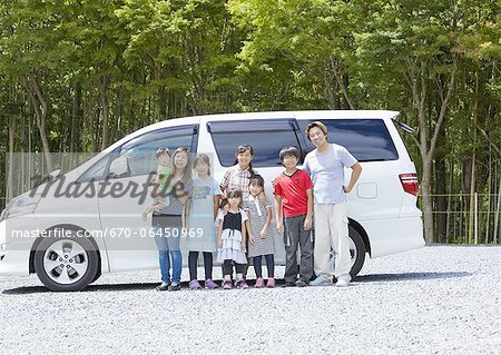 Big family in a row standing in front of a car Stock Photo - Premium Royalty-Free, Image code: 670-06450969