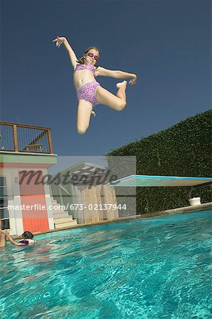 Girl leaping into a swimming pool. Stock Photo - Premium Royalty-Free, Image code: 673-02137944