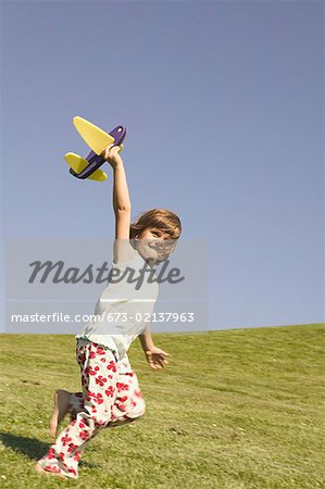 Young girl holding a toy airplane. Stock Photo - Premium Royalty-Free, Image code: 673-02137963