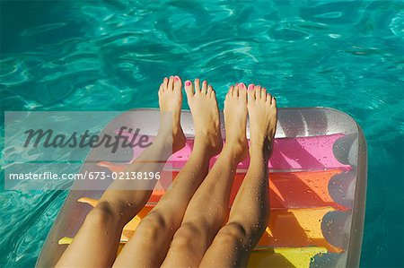Two pairs of girls' legs on a raft. Stock Photo - Premium Royalty-Free, Image code: 673-02138196