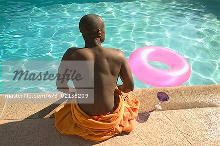 Rear view of a man sitting at poolside. Stock Photo - Premium Royalty-Free, Image code: 673-02138209