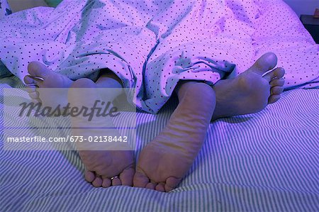 A couple's feet sticking out from under the bedcovers. Stock Photo - Premium Royalty-Free, Image code: 673-02138442