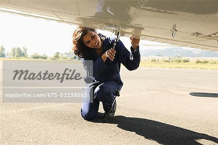 Female mechanic working on underside of airplane wing.