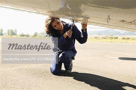 Female mechanic working on underside of airplane wing.