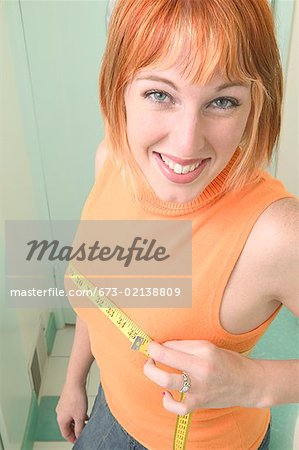 Woman measuring her chest with a measuring tape Stock Photo - Premium Royalty-Free, Image code: 673-02138809