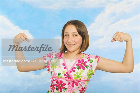 A teenaged girl flexing her muscles Stock Photo - Premium Royalty-Free, Image code: 673-02138881