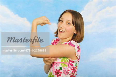 A teenaged girl flexing her muscles