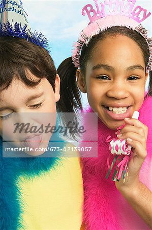 Boy and girl in party hats Stock Photo - Premium Royalty-Free, Image code: 673-02139057
