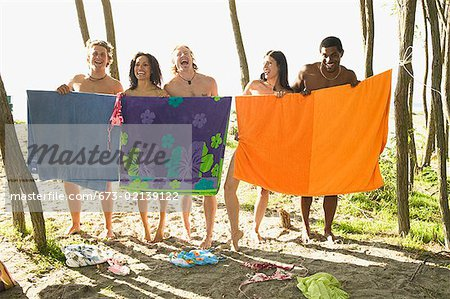 Men and women hiding behind beach towels Stock Photo - Premium Royalty-Free, Image code: 673-02139122