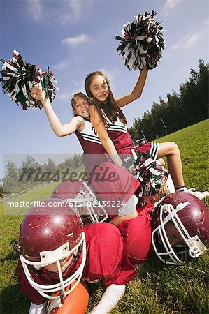 Cheerleaders sitting on football players Stock Photo - Premium Royalty-Free, Image code: 673-02139224