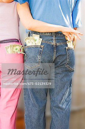 Woman taking money from man's pocket Stock Photo - Premium Royalty-Free, Image code: 673-02139329