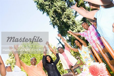 Family with upraised arms at picnic Stock Photo - Premium Royalty-Free, Image code: 673-02139616