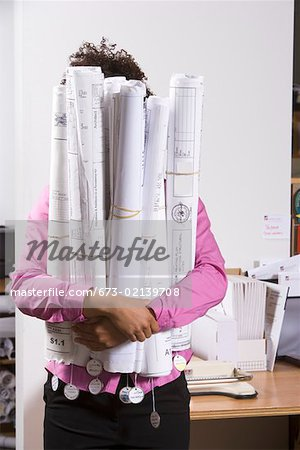Woman holding bundle of blueprints Stock Photo - Premium Royalty-Free, Image code: 673-02139708