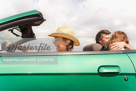 Girl pretending to drive while parents kiss Stock Photo - Premium Royalty-Free, Image code: 673-02139715