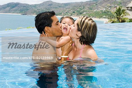 Parents kissing toddler in tropical pool Stock Photo - Premium Royalty-Free, Image code: 673-02139969
