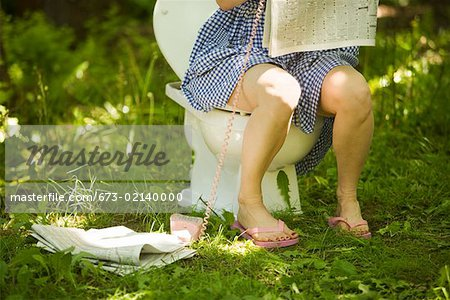 Woman sitting on toilet in grass Stock Photo - Premium Royalty-Free, Image code: 673-02140000
