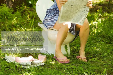 Woman reading on toilet in grass Stock Photo - Premium Royalty-Free, Image code: 673-02140012
