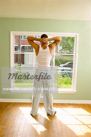 Man standing in front of window in pajamas Stock Photo - Premium Royalty-Free, Image code: 673-02140237