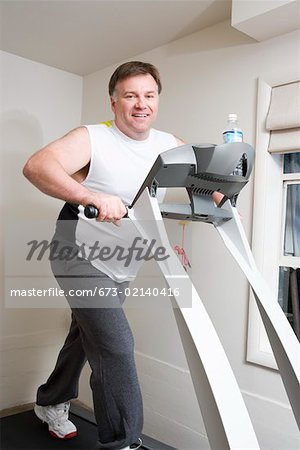 Portrait of overweight man on treadmill Stock Photo - Premium Royalty-Free, Image code: 673-02140416
