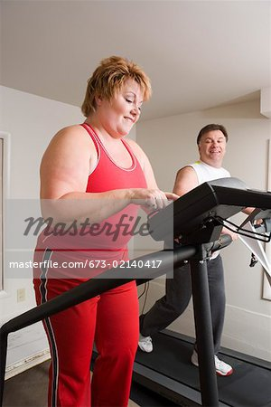 Overweight couple using exercise machines Stock Photo - Premium Royalty-Free, Image code: 673-02140417