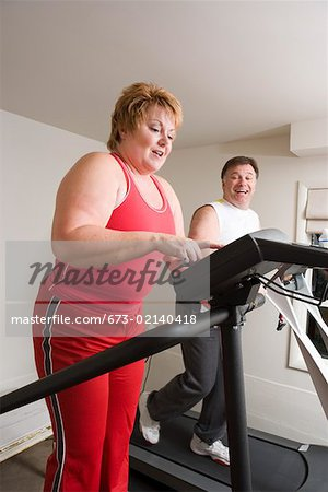 Overweight couple using exercise machines Stock Photo - Premium Royalty-Free, Image code: 673-02140418