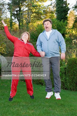 Middle aged couple jumping outdoors Stock Photo - Premium Royalty-Free, Image code: 673-02140419