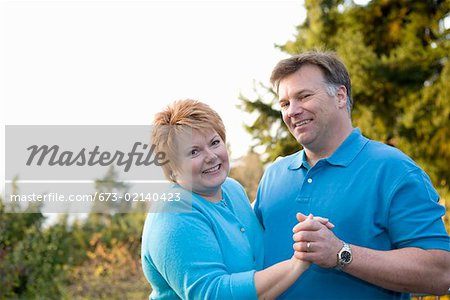 Portrait of middle aged couple dancing outside Stock Photo - Premium Royalty-Free, Image code: 673-02140423