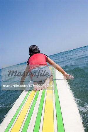 Young girl paddling surfboard Stock Photo - Premium Royalty-Free, Image code: 673-02140740
