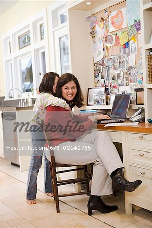 Daughter hugging mom at desk in kitchen Stock Photo - Premium Royalty-Free, Image code: 673-02140785