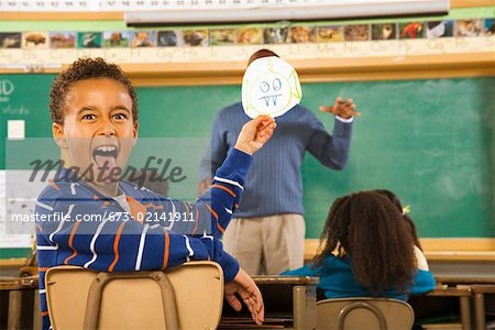 Boy holding drawing over teacher's face Stock Photo - Premium Royalty-Free, Image code: 673-02141911
