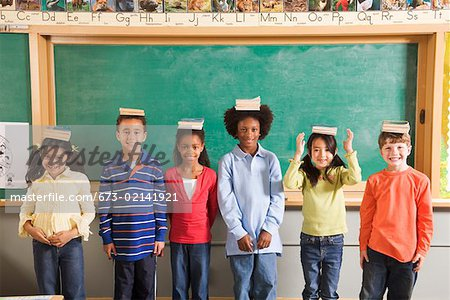 Row of students with books on their heads in classroom Stock Photo - Premium Royalty-Free, Image code: 673-02141921
