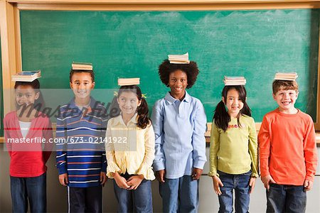 Row of students with books on their heads in classroom Stock Photo - Premium Royalty-Free, Image code: 673-02141922