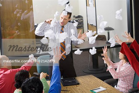 Businesspeople throwing paper at meeting Stock Photo - Premium Royalty-Free, Image code: 673-02142279