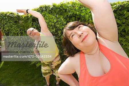 Couple stretching in backyard Stock Photo - Premium Royalty-Free, Image code: 673-02142334