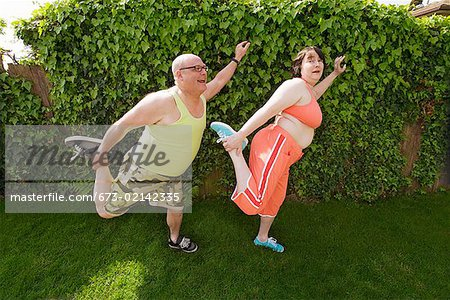 Couple stretching in backyard Stock Photo - Premium Royalty-Free, Image code: 673-02142335
