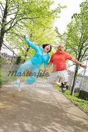 Couple jumping outside Stock Photo - Premium Royalty-Free, Image code: 673-02142341