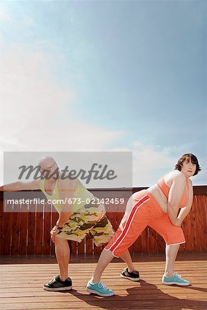Couple stretching on patio Stock Photo - Premium Royalty-Free, Image code: 673-02142459