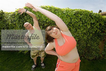 Couple stretching in backyard Stock Photo - Premium Royalty-Free, Image code: 673-02142460