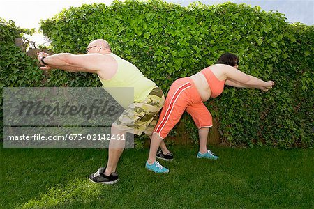 Couple stretching in backyard Stock Photo - Premium Royalty-Free, Image code: 673-02142461