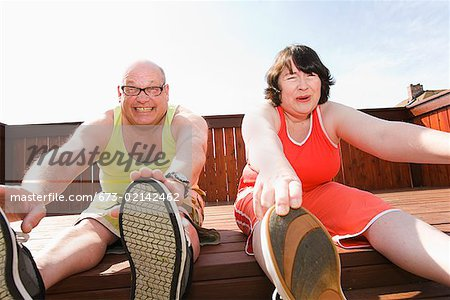 Couple stretching on patio Stock Photo - Premium Royalty-Free, Image code: 673-02142462