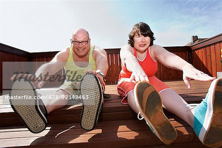Couple stretching on patio Stock Photo - Premium Royalty-Free, Image code: 673-02142463