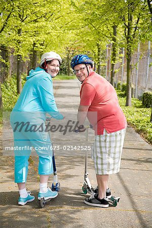 Couple riding scooters Stock Photo - Premium Royalty-Free, Image code: 673-02142525