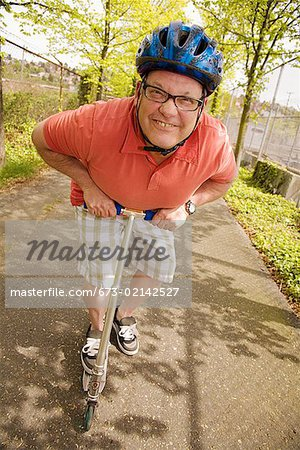 Man riding a scooter Stock Photo - Premium Royalty-Free, Image code: 673-02142527