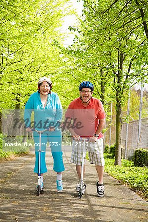 Couple riding scooters together Stock Photo - Premium Royalty-Free, Image code: 673-02142543