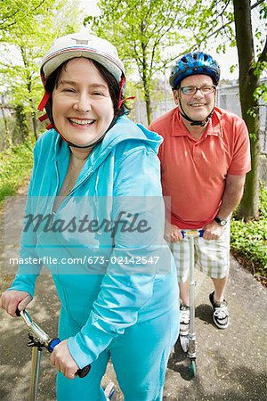 Couple riding scooters together Stock Photo - Premium Royalty-Free, Image code: 673-02142547