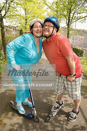Couple riding scooters together Stock Photo - Premium Royalty-Free, Image code: 673-02142548